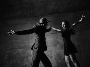 Man and woman dancing urban dancing theme concrete building surroundings black and white image